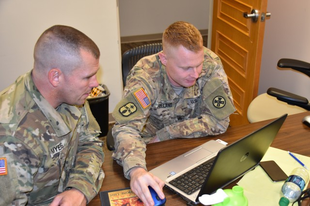 From left, Sgt. 1st Class Christopher Myers and Staff Sgt. Zachary Freeland discuss an exercise scenario during the 410th Contracting Support Brigade culminating event and external evaluation Aug. 7 at Joint Base San Antonio-Fort Sam Houston, Texas, as part of a unit contingency contracting exercise. Myers and Freeland are both with the Ohio National Guard's 1937th Contracting Team.