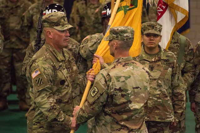 Command Sgt. Maj. Gregory Kleinholz, left, accepts the 14th MP Bde. colors from Col. Curtis Schroeder, brigade commander, signifying his taking responsibility of the brigade during a ceremony held Aug. 16 in Swift Gym.