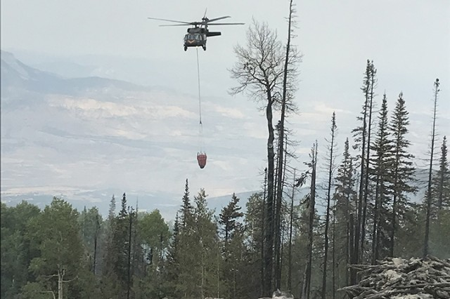 UH-60 Black Hawk helicopters, equipped with aerial water buckets, from the Chief Warrant Officer 5 David R. Carter Army Aviation Support Facility based at Buckley Air Force Base, Aurora, Colorado, drop water on the Cache Creek Fire, in Garfield County, Colorado, to support fire suppression efforts Aug. 17, 2018. The team, with two UH-60s, arrived and began operations Aug. 14.