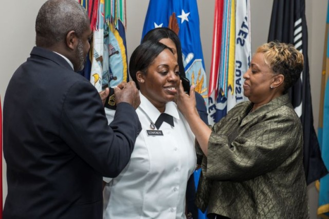 Master Sgt. Yvette Edmonds (center), a religious affairs specialists, Arlington National Cemetery, is pinned by her parents, Monica and Everette Carr, during her promotion ceremony, at the Women in Military Service for America Memorial, Arlington, Virginia, Jan. 22, 2018. The ceremony was hosted by U.S. Army Chaplain (Maj.) Willie Mashack and U.S. Air Force Chaplain (Lt. Col.) David Mansberger with the Oath of the NCO conducted by U.S. Army Chaplain (Lt. Col.) Sid Taylor. (U.S. Army photo by Elizabeth Fraser / Arlington National Cemetery / released)