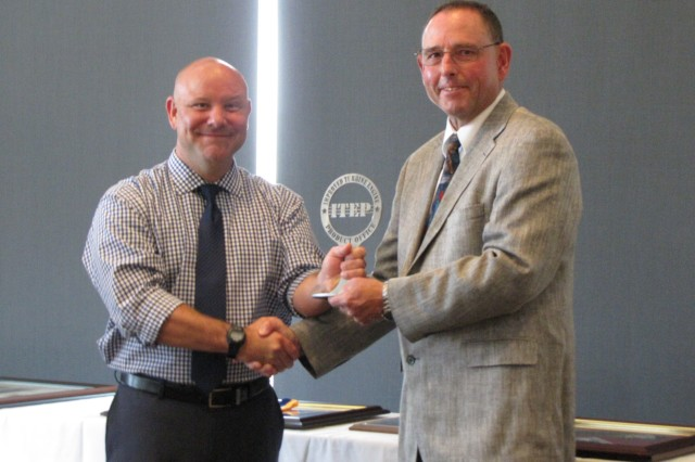Mike McCall, left, receives a memento from ITEP Deputy Project Manager Ben Plummer during a farewell ceremony celebrating his retirement from federal service.