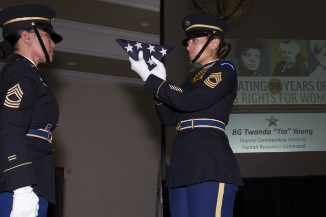 Human Resources Command Soldiers Program Support Division Senior Enlisted Advisor, Master Sgt. Joanna Carter (right) inspects an American flag before presenting it to HRC G3 Operations NCOIC, Master Sgt. Ruti Romero (left) as part of a flag-folding ceremony, as part of Fort Knox's Women's Equality Day observance, Aug. 24, at the Saber and Quill. The observance was hosted by 4th Cavalry Multi-Functional Training Brigade. (U.S. Army photo by Sgt. 1st Class Gary J. Cooper / 4th Cavalry Multi-Functional Training Brigade)