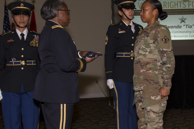 U.S. Army Human Resources Command Deputy Commanding General, Brig. Gen. Twanda E. Young (left) presents an American flag to Private Justine-Kay Ragsac during a Women's Equality Day observance at the Saber and Quill, Aug. 24, at Fort Knox. During the ceremony, hosted by 4th Cavalry Multi-Functional Training Brigade, Young called upon the women present to empower the next generation of women. (U.S. Army photo by Sgt. 1st Class Gary J. Cooper / 4th Cavalry Multi-Functional Training Brigade)