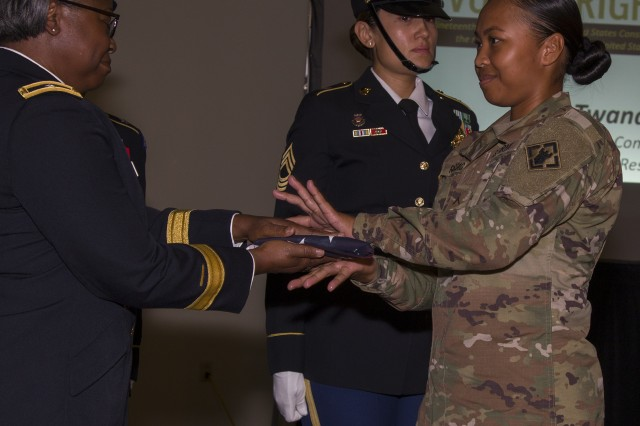 U.S. Army Human Resources Command Deputy Commanding General, Brig. Gen. Twanda Young (left) presents an American flag to Private Justine-Kay Ragsac during a Women's Equality Day observance at the Saber and Quill, Aug. 24, at Fort Knox. During the ceremony, hosted by 4th Cavalry Multi-Functional Training Brigade, Young called upon the women present to empower the next generation of women. (U.S. Army photo by Sgt. 1st Class Gary J. Cooper / 4th Cavalry Multi-Functional Training Brigade)