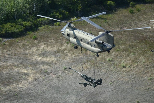 A CH-47 Chinook helicopter from 2nd General Support Aviation Battalion, 135th Aviation Regiment, Colorado Army National Guard, airlifts an M777 105mm Howitzer from Camp Grayling, Mich. to an area in the vicinity of the Combat Readiness Training Center in Alpena, Mich. Aug. 10, 2018.