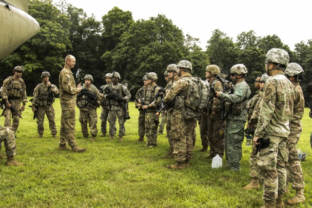 Army National Guard Soldiers from the Northeast Region at Infantry reclassification course 18-002, along with course support staff, receive a safety brief for the CH-47 Chinook helicopter before flying out for their final field training exercise at Camp Smith Training Site, Cortlandt Manor, N.Y., Aug. 7, 2018.