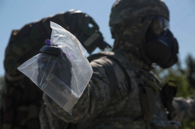 "A Soldier assigned to the 1st Area Medical Laboratory, a subordinate unit of the 20th Chemical Biological Radiological, Nuclear, Explosives (CBRNE) Command, screens a teammate for contamination while delivering a ""hazardous"" sample during their culminating training event at Lauderick Creek near Aberdeen Proving Ground, Maryland on Aug. 14. The purpose of the exercise is to practice on mission critical tasks in order to increase the unit's deployment readiness. Some of these tasks were tactical movement, reaction to enemy fire, casualty care, detection of chemical, biological, and radiological threats, and shipment of theater-validated samples to specific U.S. labs. (U.S. Army photo by Pfc. Joshua Hugley, 55th Signal Company)"