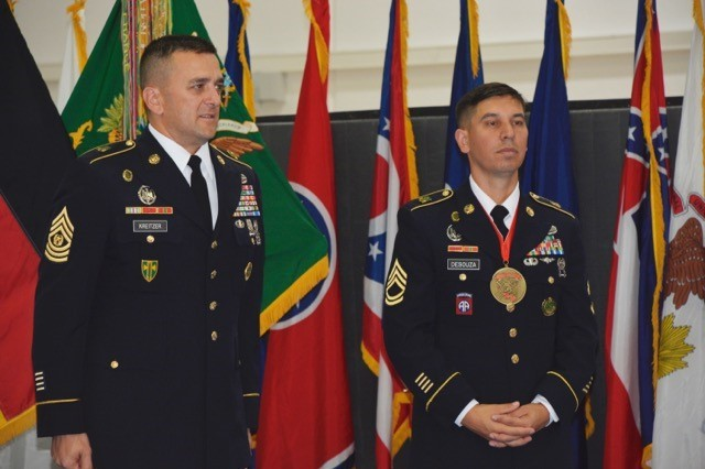 Command Sgt. Maj. Joshua M. Kreitzer and Sgt. 1st Class Wesley T. De Souza, 709th MP Bn., stand ready to receive and congratulate the 38 new NCOs after they sign the charge of the NCO.