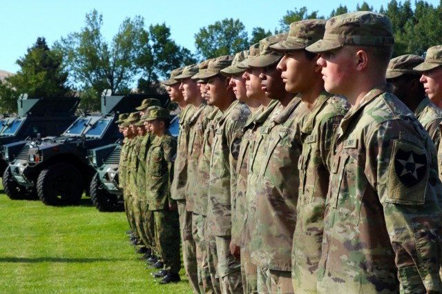 American Soldiers from Able Company, 1st Battalion, 17th Infantry Regiment, along with Soldiers from the Japanese Ground Self Defense Force, stand together in formation during the opening ceremony for Exercise Rising Thunder 18 at the Yakima Training Center, Washington, Aug. 31, 2018. This exercise is designed to better the relationships between both forces and enhance our partner capacity. (U.S. Army photo by Staff Sgt. Frances Ariele Tejada.)
