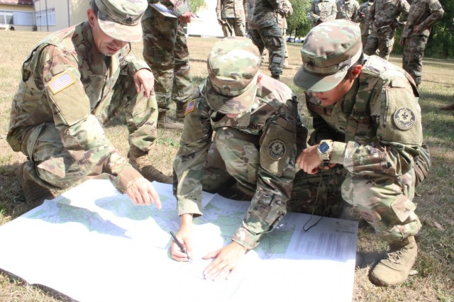 Non-commissioned officers from the Regimental Support Squadron review and test their map reading abilities during land navigation training during the team leader course at Rose Barracks, Germany, Aug. 21, 2018.  (U.S. Army photo by Spc. Austin Bistolfi, 2d Cavalry Regiment)