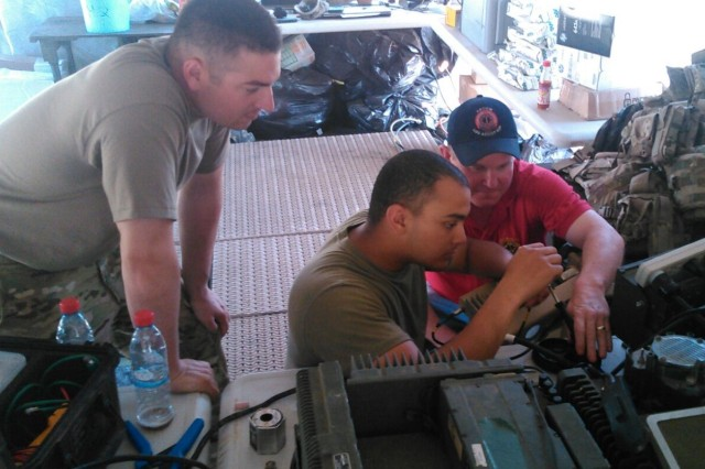 Denny Caswell, Logistic Assistance Representative, AFSBn - Germany, assists Sgt.  Justin Romero and Spec. Jason Graves (right), 277th Aviation Support Battalion, 10th  Mountain Division, with setting up the Combat Service Support Very Small Aperture Terminal in accordance with country specific requirements during Operation Atlantic Resolve, Bulgaria, July 1, 2017. (Photo by U.S. Army, provided by Denny Caswell)