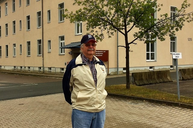 Frank Heining poses in front of his former Soldiers barracks, now home to USAG Ansbach Headquarters & Headquarters Detachment (HHD), during a  visit to Barton Baracks in Ansbach Sept. 4, 2018. (Photo by Bianca Sowders, USAG Ansbach Public Affairs)