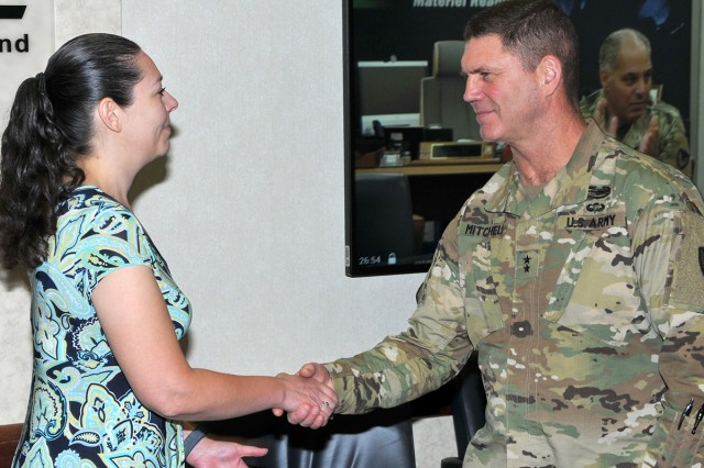 TACOM ILSC employee Kat Szalek received an AMC coin by TACOM Commander Maj. Gen. Daniel Mitchell on AMC Commander Gen. Gustave Perna's behalf, with Perna watching via video teleconference.
