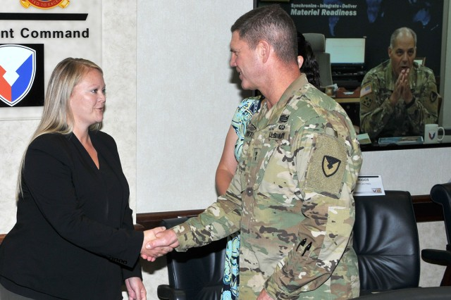 TACOM ILSC employee Brandie Jackowski received an AMC coin by TACOM Commander Maj. Gen. Daniel Mitchell on AMC Commander Gen. Gustave Perna's behalf, with Perna watching via video teleconference.