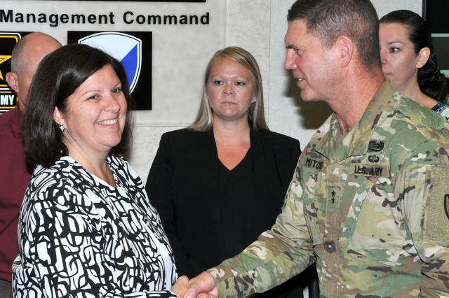 TACOM ILSC employee Julie Jacobs received an AMC coin by TACOM Commander Maj. Gen. Daniel Mitchell on AMC Commander Gen. Gustave Perna's behalf.