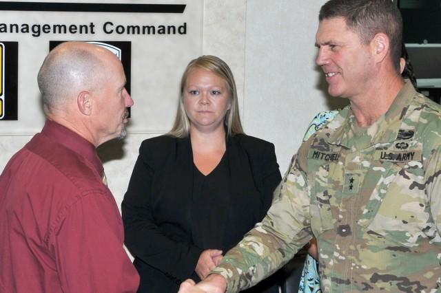 TACOM ILSC employee Paul Webster received an AMC coin by TACOM Commander Maj. Gen. Daniel Mitchell on AMC Commander Gen. Gustave Perna's behalf.