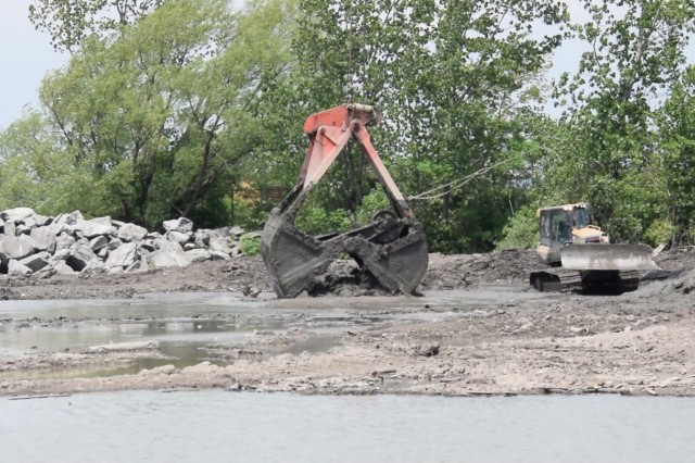 A USACE contractor uses a clamshell attached to a crane to place dredged materials at a site designated for wetland habitat restoration on Unity Island in Buffalo, NY June 1, 2018. The dredged materials come from the Niagara River alongside the Black Rock Lock, close to the project site. (Photo by Dr. Michael Izard-Carroll)