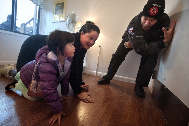Will Silva, right, Joint Base Lewis-McChord fire inspector, shows Christy Aguirre, of JBLM, and her daughter, Amelia, 4, how to feel a door to detect fire during a fire safety lesson inside the JBLM Fire Prevention Trailer at the JBLM Fire and Emergency Services booth at the Lewis Main Exchange in 2017.