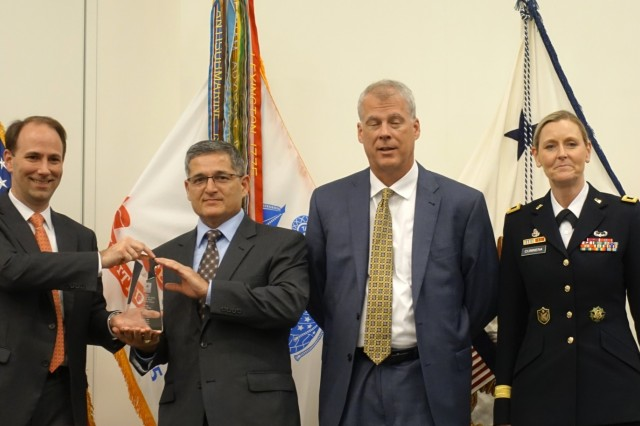 Jordan Gillis, acting assistant secretary of the army installations, Energy & Environment (ASA IE&E), left, awards Victor Lopez, director infrastructure and risk management, Corpus Christi Army Depot, middle left, with a trophy acknowledging CCAD as a winner of the 2018 Secretary of the Army Energy and Water Management Award, energy conservation category, during a ceremony, Cleveland, Ohio, August 23, 2018. Also in photo is Mark Krog, Siemens contractor, and Brig. Gen. Joy Curriera, director of operations, Army Assistant Chief of Staff for Installation Management.
