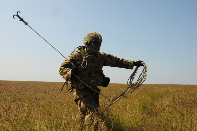 U.S. Army Pfc. Oghene Ejefiavwo, a combat engineer assigned to the 91st Engineer Battalion attached to the 2nd Battalion, 5th Cavalry Regiment, 1st Armored Brigade Combat Team, 1st Cavalry Division throws a grappling hook to help clear concertina wire during a combined arms live fire mission at Smardan Training Area, Romania, Aug. 29, 2018.