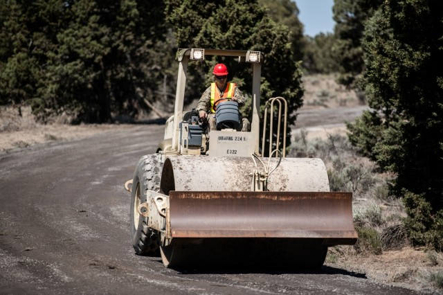 An Oregon Army National Guard Soldier with the 224th Engineer Company, 1249th Engineer Battalion, smooths out a freshly resurfaced road at Biak Training Center near Redmond, Oregon, June 19, 2018. The 224th Engineer Co. spent their 2018 annual training repairing and resurfacing several miles of gravel road on the 43,000 acres at Biak, which is open to both military training and public recreational use.