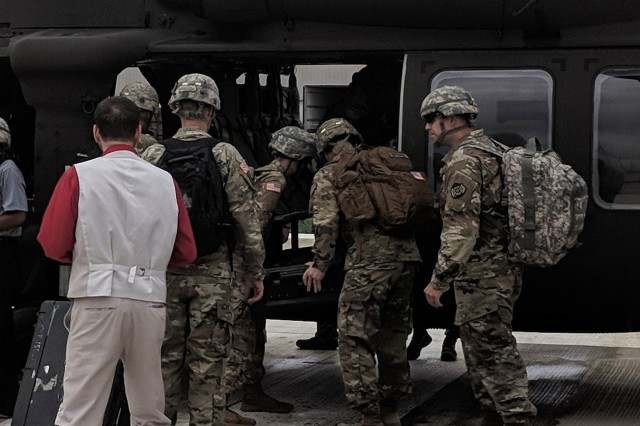 Cyber Soldiers with the Army Cyber Protection Brigade load up with their gear onto an Indiana National Guard UH-60 Black Hawk helicopter at Stout Army Airfield in Indianapolis, Aug. 17, 2018. The movement was part of the deployment of the CPB's 154th and 155th Cyber Protection Teams to exercise Operation Tiger Stance, at the Indiana Guard's Muscatatuck Urban Training Center in Butlerville, Ind. OTS was a five-day live, scenario-based situational cyberspace training exercise designed to prepare Cyber Protection Teams for task force-oriented real-world operations. (Photo by Maj. Joe Marty)