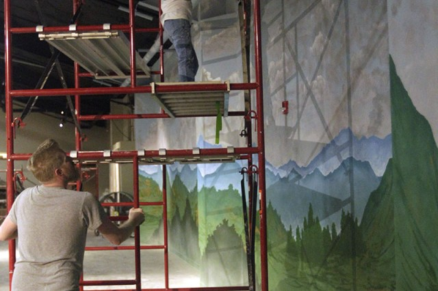 Erik Sunderman pushes the scaffold Aug. 31, 2018, into position so that his wife, Liz Mercer, can work on a particular part of the giant 52-foot by 12-foot mural that will serve as backdrop for the Vietnam War display inside the new gallery of the Army Field Artillery Museum. Artists at Large is the name of this Oklahoma City couple's business.