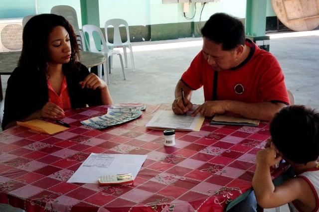 An OCS Soldier in civilian clothes provides final payment to a first-time local Philippine vendor.