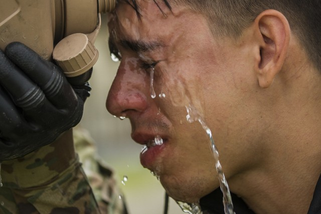 A Soldier assigned to Company B, 602nd Aviation Support Battalion, 2nd Combat Aviation Brigade, 2nd Infantry Division, rinses his skin after exposure to chlorobenzylidene malononitrile gas during chemical, biological, radiological and nuclear defense training on Camp Humphreys, Republic of Korea, May 27. CS gas can be used by military and police forces as a form of non-lethal crowd control. (U.S. Army photo by Spc. Adeline Witherspoon, 20th Public Affairs Detachment)