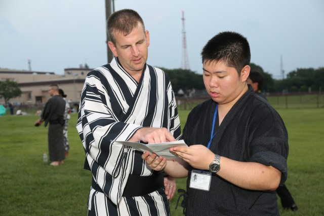 Takizawa, one of nine Japanese college students chose to take part in a summer internship program on Camp Zama, shows an event schedule to an attendee at the installation's annual Bon Odori Festival on Aug. 4. (U.S. Army photo by Noriko Kudo)