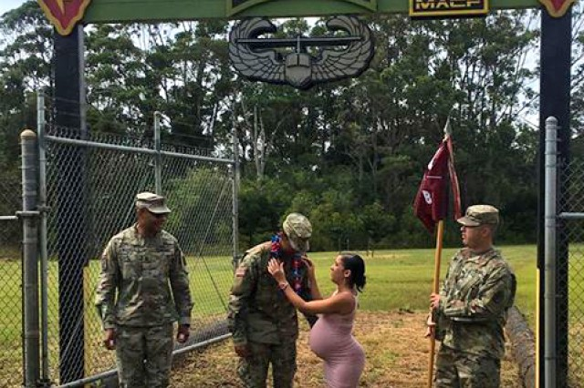 Staff Sgt. Gabriel Mejias, (center-left) noncommissioned officer in charge of TAMC's Neonatal Intensive Care Unit and combat medic, is presented with a lei by his spouse, Marlee Mejias (center-right) during the 25th Infantry Division's Jungle Operations Training Course graduation ceremony, Aug. 10. Mejias is the distinguished honor graduate of class 07-18.