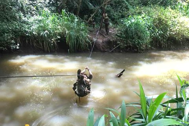 Staff Sgt. Gabriel Mejias, noncommissioned officer in charge of TAMC's Neonatal Intensive Care Unit and combat medic, uses a fixed rope to cross a river during the 25th Infantry Division's Jungle Operations Training Course, July 24 to Aug. 9, at East Range Training Center, Schofield Barracks, Hawaii, with class 07-18.