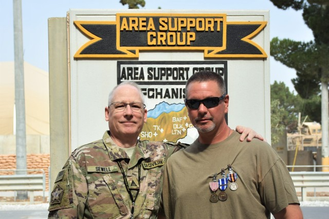 (From left) Area Support Group - Afghanistan (ASG-A) Deputy to the Commander Bill Sewell stands with Department of the Navy Civilian Jonathan Covington at the ASG-A Headquarters on Bagram Air Field. Covington was awarded the Outstanding Civilian Service Medal, NATO Medal and Global War on Terrorism Service Medal for exceptional service to ASG-A on Sept. 6.
