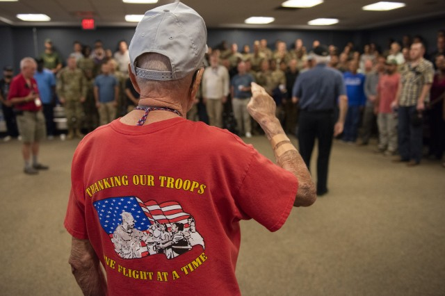 An elderly volunteer salutes a contingent of Soldiers, government civilians and contractors during their layover at the Portsmouth International Airport at Pease, N.H., Sept. 7, 2018.