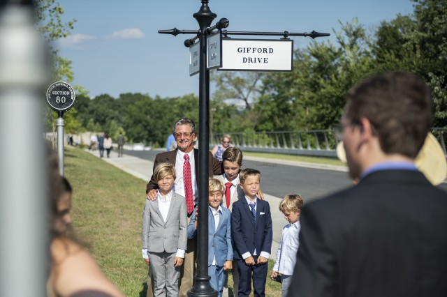 Members of the Gifford family stand under a street sign honoring U.S. Marine Corps Gunnery Sgt. Jonathan W. Gifford in the newest area of Arlington National Cemetery, also known as the Millennium site, Arlington National Cemetery, Arlington, Virginia, Sept. 6, 2018.