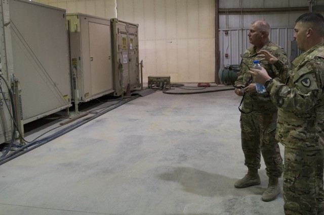 U.S. Army Capt. Joshua Paille shows his father, U.S. Air Force Chief Master Sgt. Andre Paille, some of the equipment his unit uses in helicopter maintenance at the airfield where Joshua Paille works at Camp Arifjan, Kuwait, Sept. 1, 2018.