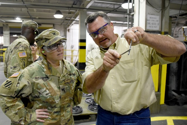 "Jeremy ""Bubba"" Harris, bomb and mines supervisor in the Industrial Operations Division, shows Col. Michelle M. T. Letcher the zinc aluminum wire used to coat the outside of conventional bomb bodies during a visit to McAlester Army Ammunition Plant, Okla., Sept. 4."