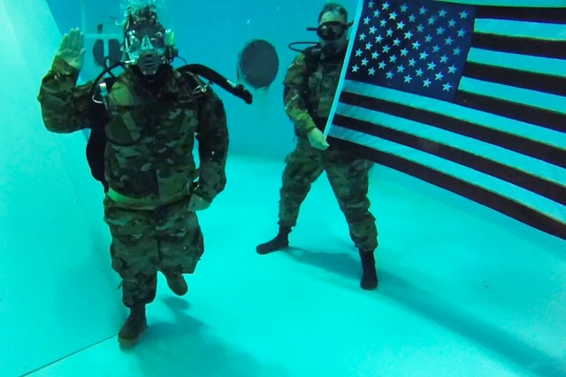 U.S. Army Staff Sgt. Michael Brown reenlists 30 feet underwater at the U.S. Space & Rocket Center, Huntsville, Alabama, Aug. 31. Brown, a U.S. Army Space and Missile Defense Command/Army Forces Strategic Command Soldier, combat veteran and Wounded Warrior was introduced to scuba diving as a part of adaptive rehabilitation following the loss of his left leg in 2007 during combat operations in Iraq. (U.S. Army Photo by Ronald Bailey)