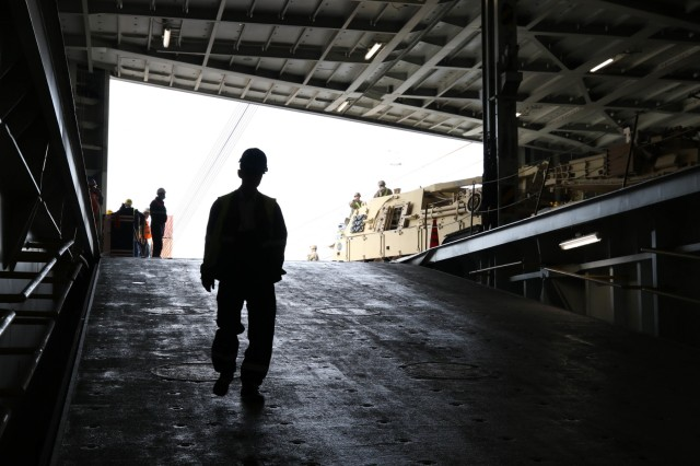 An employee with the Deepwater Container Terminal walks through the deck of the Liberty Pride deep water container ship while Soldiers with the 2nd Squadron, 278th Armored Calvary Regiment, use a M88 recovery vehicle to tow a M2 Bradley off the container ship at the port of Gdansk in Gdansk, Poland August 29, 2018.The decision to deploy the U.S. enhanced Forward Presence battle group in Poland was made exclusively because doing so will most effectively reinforce NATO's conventional deterrence.Poland is one of the four framework nations for NATO's eFP, Operation Atlantic Resolve, a nine-month training mission for reserve, National Guard and active duty units with NATO partners in the commitment to peace, security and stability in Europe. (U.S. Army photo by: Staff Sgt. Michael Eaddy)