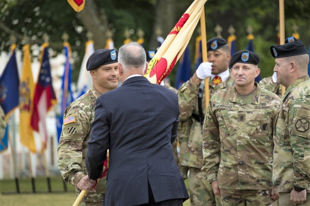 Col. Jason T. Edwards accepts the U.S. Army Garrison Rheinland-Pfalz colors from Michael D. Formica, Installation Management Command-Europe director, during a change of command ceremony at Daenner Kaserne, July 11, 2018.