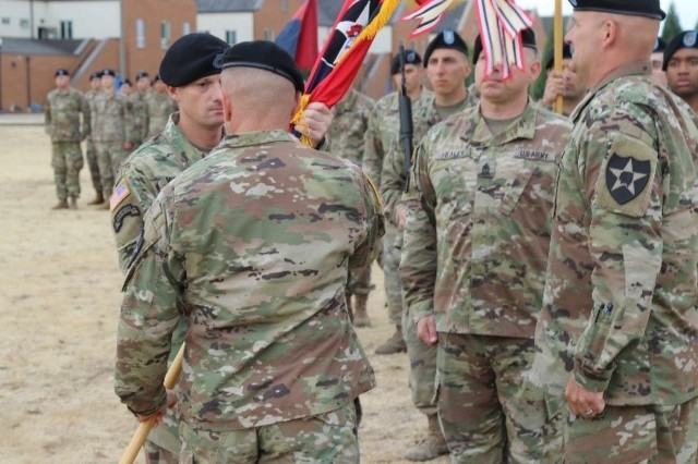 "Command Sgt. Maj. Christopher Mullinax accepts the Lancer colors from Col. Jay Miseli, commander 2nd Stryker Brigade Combat Team, 2nd Infantry Division, assuming his new responsibilities as Lancer 7 during a Change of Responsibility ceremony at Lancer Field, McChord, Aug. 23. ""I truly believe our principal duty as NCOs is to train our Soldiers, so they have the best chance to survive in combat when called upon,"" said Mullinax."
