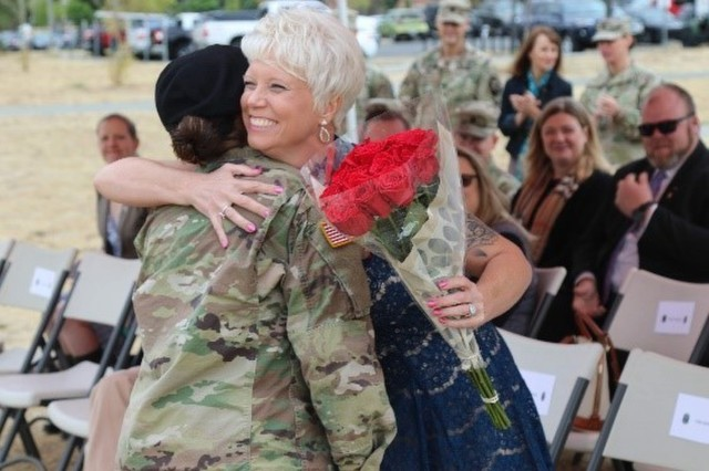 Anna Graves, wife of Command Sgt. Maj. Ronald Graves, receives a dozen roses from Lancer Brigade signifying the bonds of loyalty and affection for all her service and sacrifice on behalf of the unit, and to signify Lancer's sorrow at her departure during a Change of Responsibility ceremony at Lancer Field, Joint Base Lewis-McChord, Aug. 23.