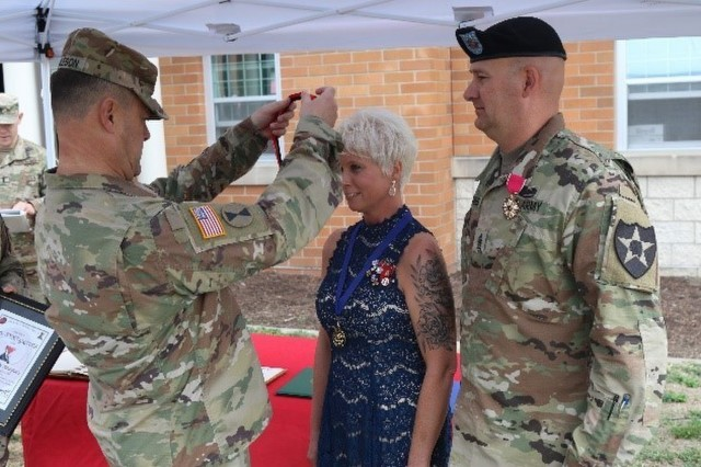 Anna Graves is inducted into 7th Infantry Divisions Keeper of the Hourglass by Maj. Gen. Willard Burleson III, 7th Infantry Division commanding general, at an award ceremony prior to the Change of Responsibility ceremony at Lancer Field, Joint Base Lewis-McChord, Aug. 23, 2018.  As a senior leader spouse, and volunteer in the Joint Base Lewis-McChord community Graves' positive impact helped improve the morale and lives of those she so selflessly served.
