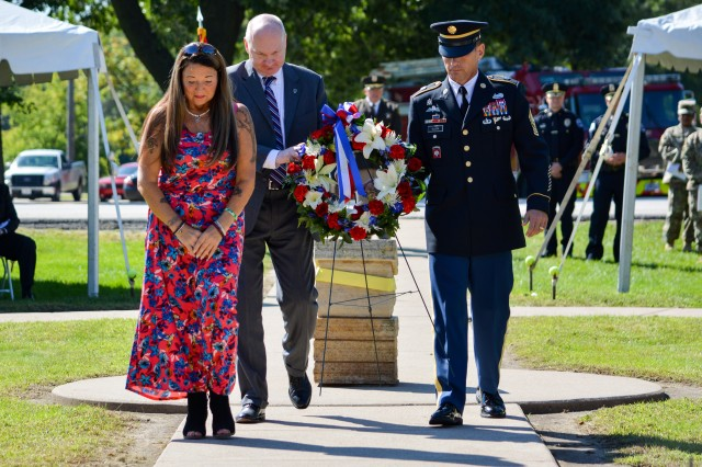 Michael Hutchison, deputy to the commander, U.S. Army Sustainment Command, and Command Sgt. Maj. Joe Ulloth, U.S. ASC, walk with Barbara Ritter, Gold Star mother of Sgt. Leevon Ritter, to place a wreath at the 9/11 Memorial, Rock Island Arsenal, Sept. 11. (Photo by Linda Lambiotte, ASC Public Affairs)