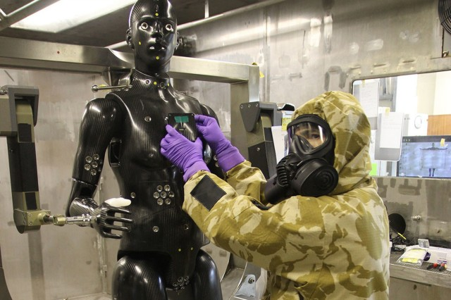 U.S. RDECOM C&B Center scientist Terrence D'Onofrio, in full CB suit protection, outfits Porton Man with sensors prior to a test.