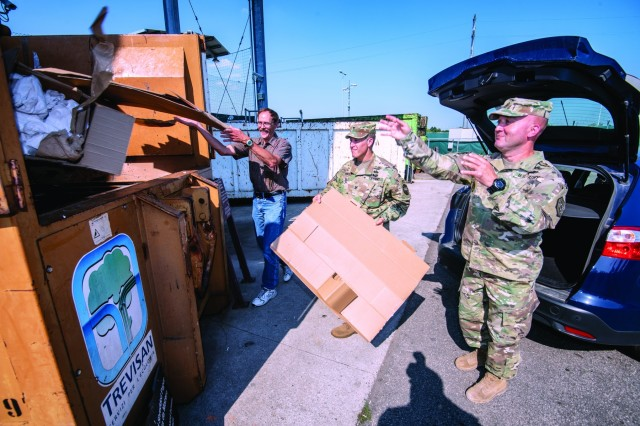 From left: Kurt Brownell, U.S. Army Garrison Italy solid waste/recycling compliance manager; Garrison Commander Col. Erik M. Berdy; and Garrison Command Sgt. Maj. Mason L. Bryant toss some cardboard into the container at the Eco Center on Caserma Ederle. On Aug. 20, Berdy signed an updated recycling policy for the Darby and Vicenza military communities.