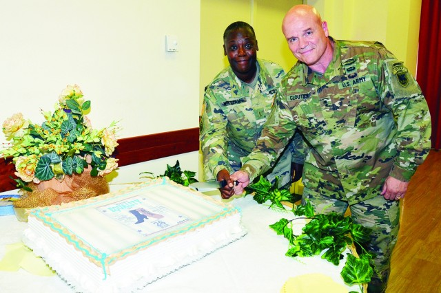 U.S. Army Africa Commander Maj. Gen. Roger L. Cloutier Jr. and Chief Warrant Officer 5 Anita Williams, USARAF G-4, prepare to cut the cake for community members to enjoy.