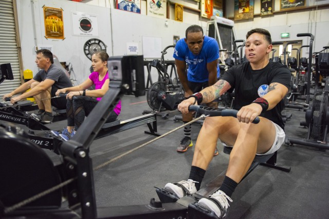 Chief Warrant Officer 2 John Goins, an Arkansas National Guardsman, coaches Cpl. Destyni Gonzales, a military police officer with Area Support Group-Kuwait, while she conducts cardio on a rowing machine inside the Combatives and Cross Training Facility on Camp Arifjan, Kuwait, Sept. 11, 2018.