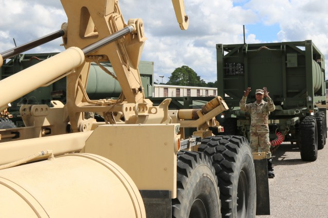 3rd Expeditionary Sustainment Command Soldier guides truck to hook up a water trailer in preparation for Hurricane Florence at Fort Bragg, North Carolina, Sept. 12, 2018.