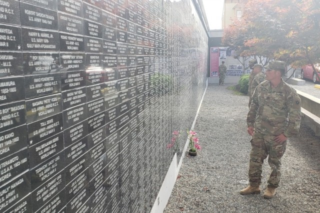 Staff Sgt. Lucas Miller searches a wall outside the Nisei Veteran's Committee Memorial Hall, looking for his Asian-American family who served during WWII in Seattle, Washington on September 10. The wall is lined with more than 3,500 bricks engraved with the names of Asian-Americans who were interned in camps in the United States due to their race, or served in the U.S. military during WWII. (U.S. Army Photo by Staff Sgt. Christopher Jelle, 5th Mobile Public Affairs Detachment)